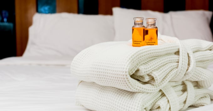 Bed with Hotel Toiletries on Top of Robes