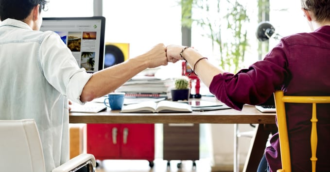 Playful Coworkers Fist Bumping
